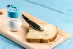Flat lay butter spread on bread with knife and saltshaker served on a wooden board.  stock image