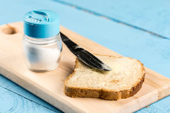 Flat lay butter spread on bread with knife and saltshaker served on a wooden board.  royalty free stock image