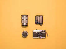 Flat Lay Camera 1. Flat Lay, Top View of Camera and photography tool on yellow background with space Stock Photo