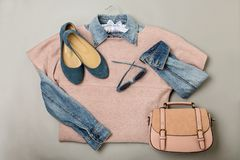 Flat lay of a casual woman fashion outfit - jeans, pink dress, h. Andbag and sunglsses. Top view on gray background. Selective focus Royalty Free Stock Photos