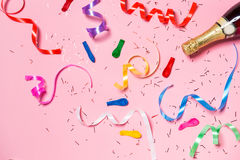 Flat lay of Celebration. Champagne bottle with colorful party st. Reamers on pink background Royalty Free Stock Photo