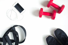 Flat lay of cellphone, red dumbbells and sport equipment on whit. E background. Sport wear, Sport fashion, Sport accessories, Sport equipment, top view Stock Image