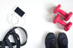 Flat lay of cellphone, red dumbbells and sport equipment on whit. E background. Sport wear, Sport fashion, Sport accessories, Sport equipment, top view Royalty Free Stock Photography