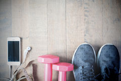 Flat lay of cellphone and sport equipment on wooden background. Stock Photos