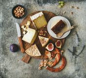 Flat-lay of cheese assortment, figs, honey, bread and nuts. Flat-lay of cheese platter with cheese assortment, figs, honey, fresh bread and nuts over grey Stock Image
