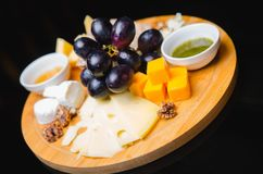 Flat-lay of cheese platter with cheese assortment, figs, honey and nuts over grey concrete background, top view. Royalty Free Stock Image