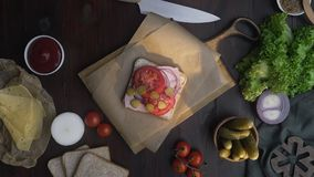 Flat lay of chef`s hand adds sliced tomato to the sandwich with ham and vegetables on the wooden board in the beam of. Light, making of the fastfood at home stock video