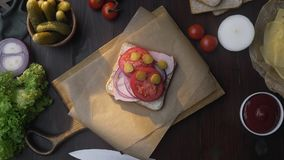 Flat lay of chef`s hand adds sliced tomato to the sandwich with ham and vegetables on the wooden board in the beam of