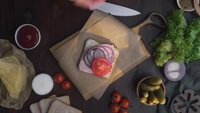 Flat lay of chef`s hand adds slised tomatoes to the sandwich with ham and vegetables on the wooden board in the beam of