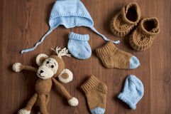 Flat lay children's knitted clothing and monkey  toy. On wooden background Royalty Free Stock Image