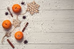 Flat lay. White rustic table with tangerines, cinnamon sticks, anise-star, wooden snowflakes, artificial snow. Copy space stock photo