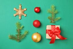 Christmas composition with gift box and festive decor on color background. Flat lay Christmas composition with gift box and festive decor on color background Stock Photography