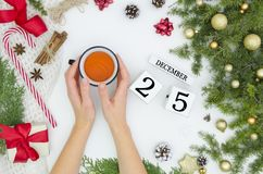 Flat lay of Christmas decoration ornaments on white background and woman hand holding cup of tea - Trendy minimal flat royalty free stock photo