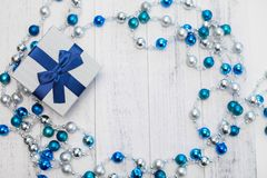 Flat lay Christmas gift with blue ribbon and silver and blue Christmas balls on white wooden background.  royalty free stock images