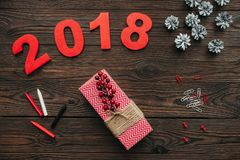 Flat lay with christmas gifts, pine cones and 2018 year sign on dark. Wooden tabletop royalty free illustration