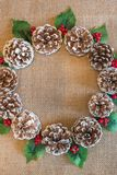 Flat lay Christmas wreath of pinecones, red berries, and holly leaves royalty free stock photography