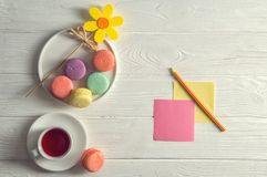 Flat lay. Close up. Bright colorful french macarons, yellow felt flower, a cup of berry tea, a pencil, stickers. Copy space. Flat lay. Close up. Bright colorful royalty free stock image