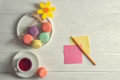 Flat lay. Close up. Bright mood. Colorful french macarons, yellow felt flower, a cup of berry tea, a pencil, stickers. Copy space. Flat lay. Close up. Bright royalty free stock photos