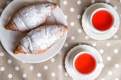 Flat lay, close up. Freshly baked French croissants and berry tea. Vintage white china, polka dot pastel napkin royalty free stock photo