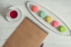 Flat lay. Close up. Provence breakfast. Bright colorful macarons, brown vintage notebook, a pen, a cup of berry tea. Copy space stock photos