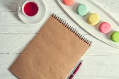Flat lay. Close up. Provence morning. Bright colorful macarons, brown vintage blank, a pen, a cup of berry tea. Copy space royalty free stock photos