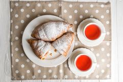Flat lay, close up. Romantic breakfast for two. Freshly baked French croissants and berry tea. One of the croissants is cut. stock photo