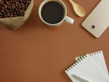 Flat lay coffee with smartphone and notebook and copy space. Flat lay,top view a cup of coffee,notebook,pen and smartphone on brown desk with copy space Stock Image