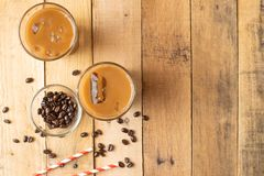 Flat lay. Cold coffee in transparent glasses with ice and straws, on a wooden background, cooling drink, refreshing, summer mood,. With copy space royalty free stock photography