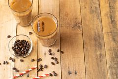 Flat lay. Cold coffee in transparent glasses with ice and straws, on a wooden background, cooling drink, refreshing, summer mood,. With copy space royalty free stock photos