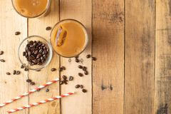 Flat lay. Cold coffee in transparent glasses with ice and straws, on a wooden background, cooling drink, refreshing, summer mood,. With copy space stock photography