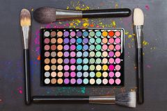 Flat lay of colorful eyeshadow palette with brushes on black background. Flat lay of colorful eyeshadow palette with professional brushes on black background royalty free stock photos