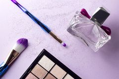 Flat lay colorful make up set with unicorn glitter on pastel purple background stock photos