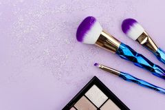 Flat lay colorful make up set with unicorn glitter on pastel purple background royalty free stock image