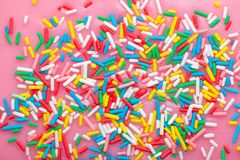 Flat lay of colorful sprinkles on glaze background, top view. Flat lay of colorful sprinkles on glaze pink background, top view royalty free stock photography