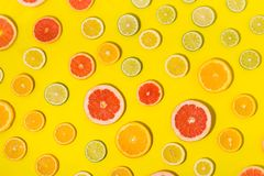 Flat lay colorful summer background lemon lime orange grapefruit. Flat lay colorful summer background. Different citrus fruits on yellow background close up. Top royalty free stock image