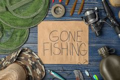 Flat lay composition of angling equipment. And paper with words `GONE FISHING` on wooden background royalty free stock image