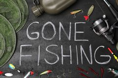 Flat lay composition with angling equipment and words. `GONE FISHING` on dark background stock photos