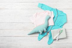 Flat lay composition with baby clothes and accessories. On wooden background. Space for text stock images