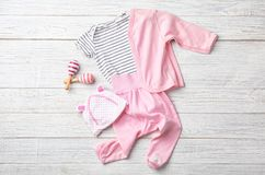 Flat lay composition with baby clothes and accessories. On wooden background royalty free stock photography