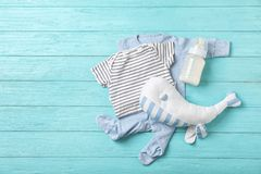 Flat lay composition with baby clothes and accessories. On wooden background. Space for text stock image
