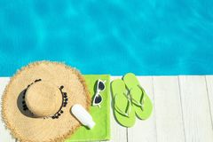 Flat lay composition with beach accessories on wooden deck near swimming pool. Space for text stock photography