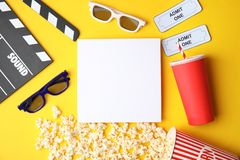 Flat lay composition with blank paper, popcorn and clapper on color background, mockup for design. stock photo