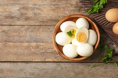 Flat lay composition with boiled eggs and space for text. On wooden background stock image