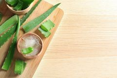 Flat lay composition with bowl of peeled aloe vera, green leaves and space for text. On wooden table stock image