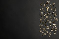 Flat lay composition with bronze vintage ornate keys on dark background. Space for text royalty free stock photos
