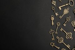 Flat lay composition with bronze vintage ornate keys on dark background. Space for text royalty free stock image