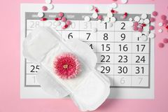 Flat lay composition with calendar, menstrual pad. And pills on color background. Gynecological checkup royalty free stock photography