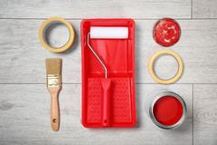 Flat lay composition with can of paint and decorator tools. On wooden background stock photo