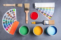 Flat lay composition with cans of paint, brushes and color palette samples. On gray background stock photos
