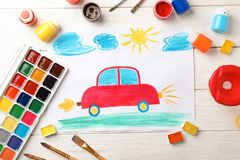 Flat lay composition with child`s painting of car. On table stock image